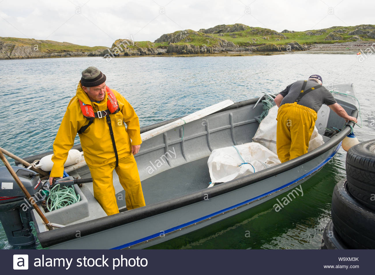 Irish man wearing yellow slicker rain suit and automatic inflating personal floatation device operating outboard motor in small boat Stock Photo