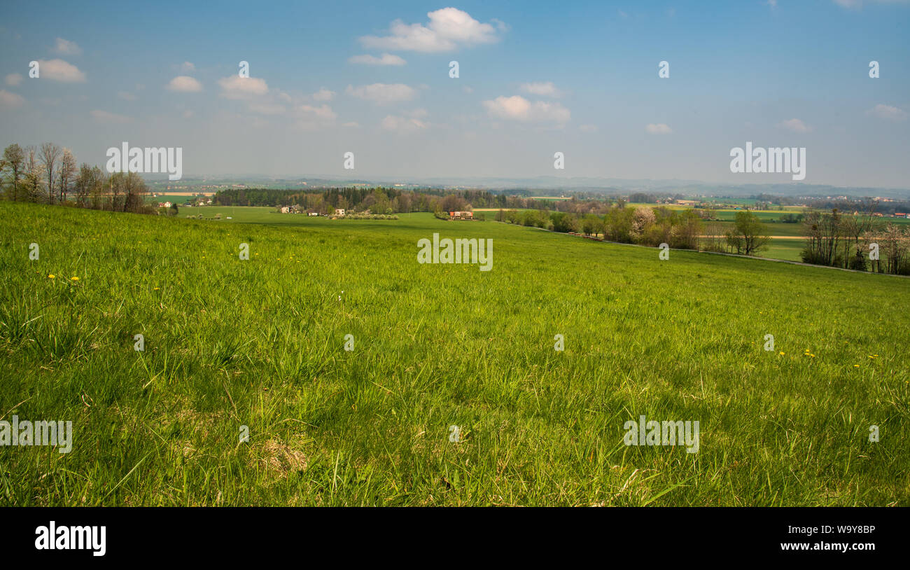 springtime rural scenery with meadows, fields, forest and dispersed settlement from road above Komorni Lhotka village bellow Prasiva hill in Moravskos Stock Photo