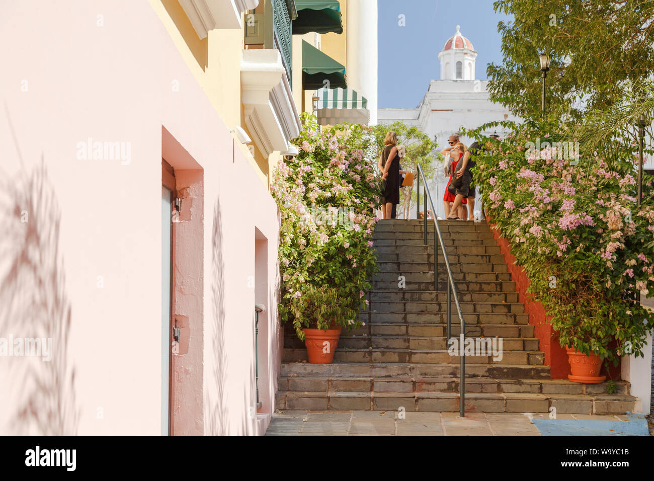 People chat on top of the flower filled stairs at Plaza de la Catedral located in front of San Juan Bautista Cathedral in Old San Juan, San Juan, PR. Stock Photo