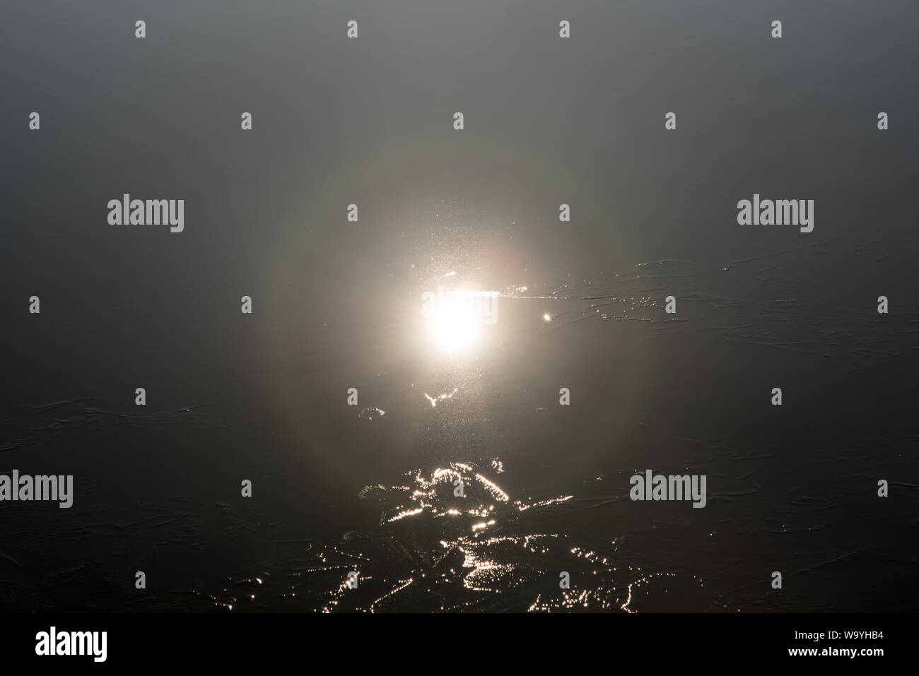 sun reflection on partly frozen lake water ground Stock Photo