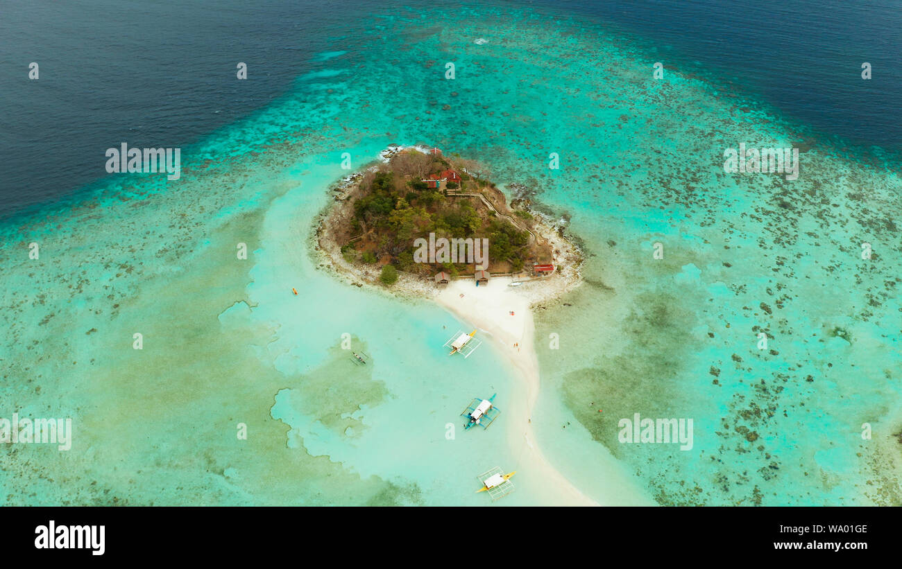 aerial seascape tropical island and sand beach, turquoise water and coral reef. malacory island, Philippines, Palawan. tourist boats on coast tropical island. Stock Photo