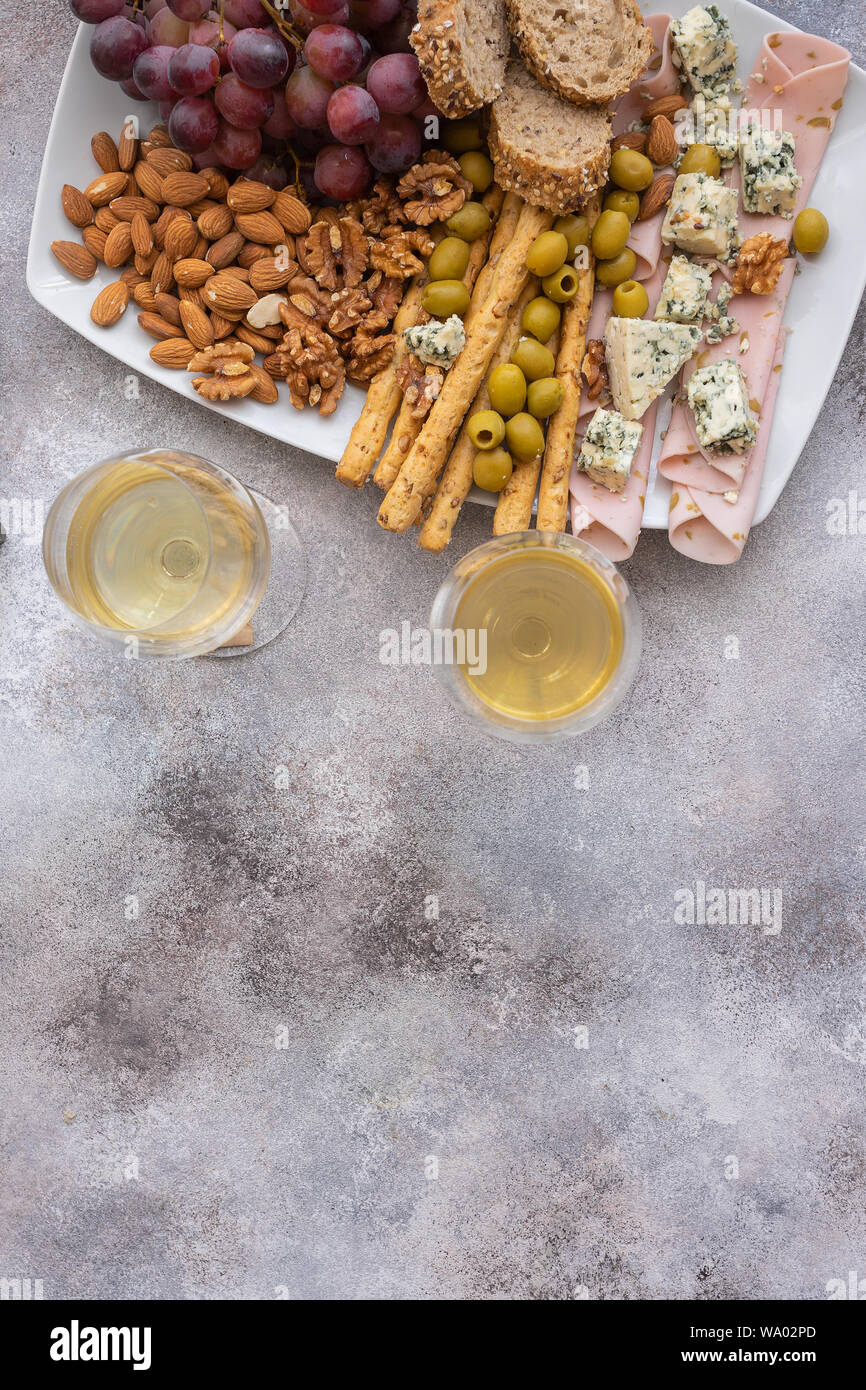 Two glasses of white wine and plate with different snacks. Blue cheese, olives, baguette slices, grissini, ham, grapes and nuts. Wine snacks set backg Stock Photo