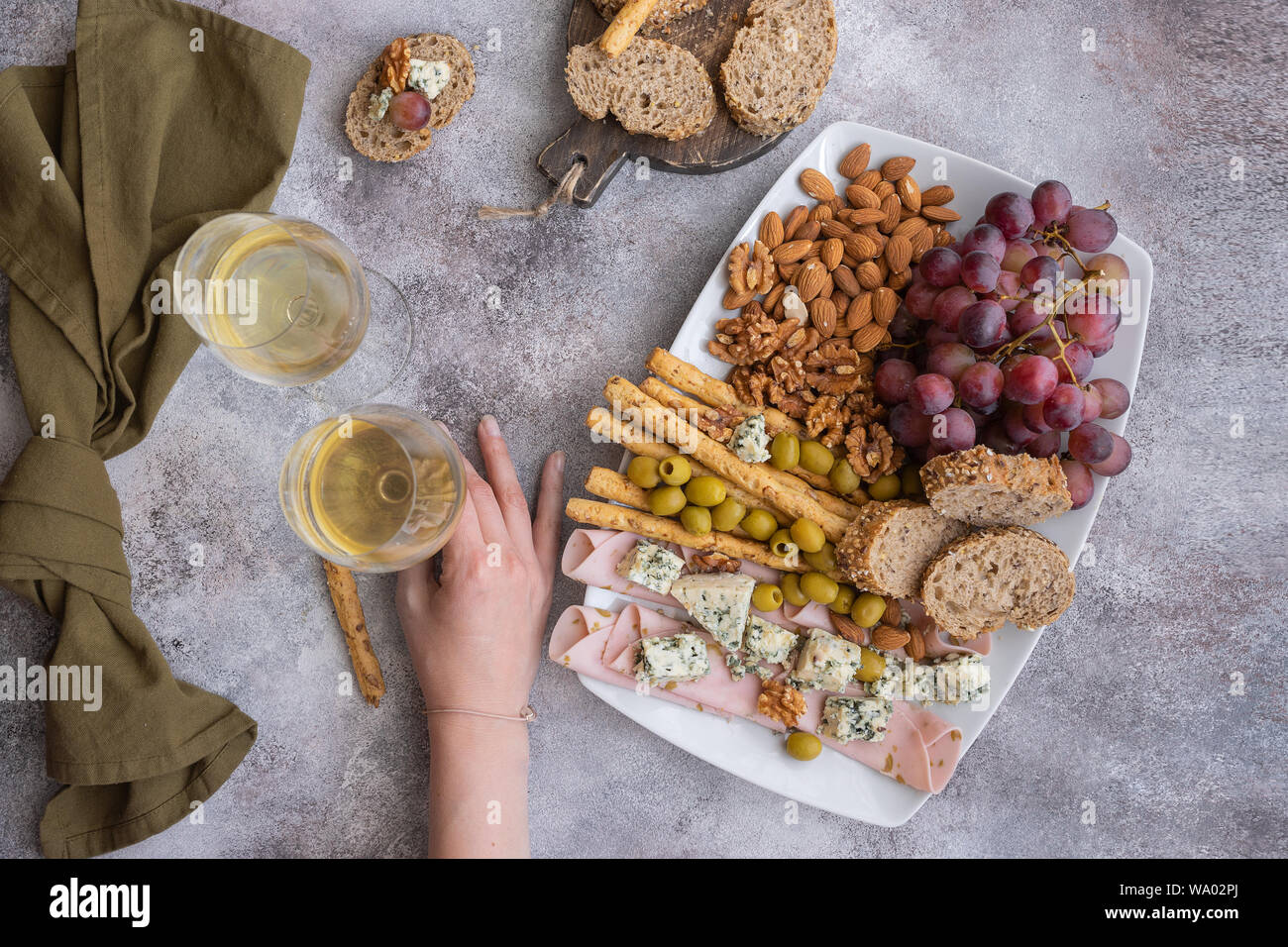 Two glasses of white wine and plate with different snacks.Female hand holding glass of wine .Tasting party background. Top view. Stock Photo