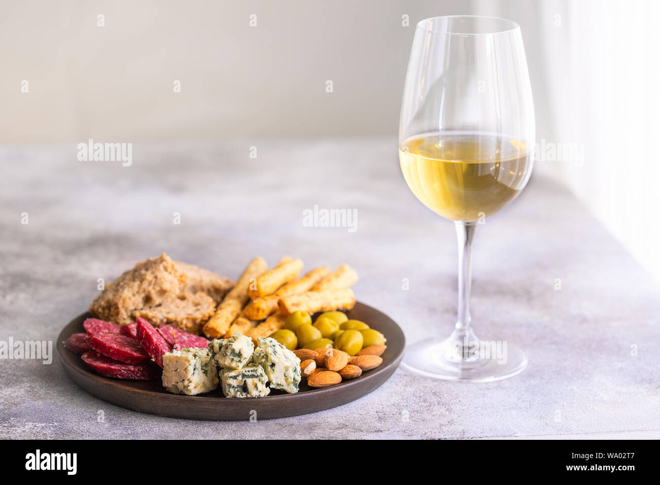 Glass Of White Wine And Plate With Different Snacks Blue Cheese Olives Baguette Slices Cured Meat Grapes And Nuts Wine Snacks Set Background Stock Photo Alamy