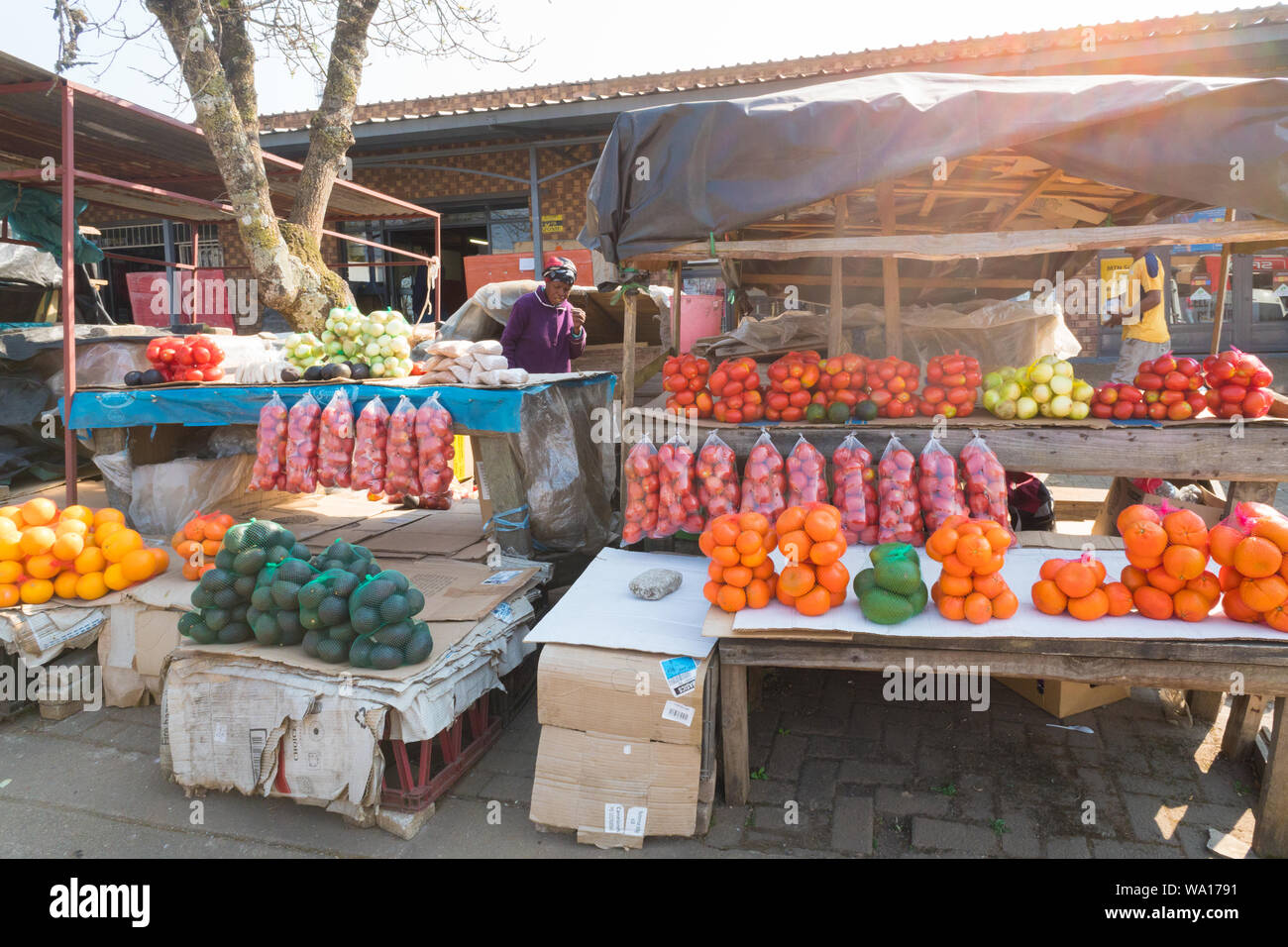 Black African lady or woman at her street vendor stall which displays a selection of bags of fruit and vegetables in Graskop, Mpumalanga, South Africa Stock Photo
