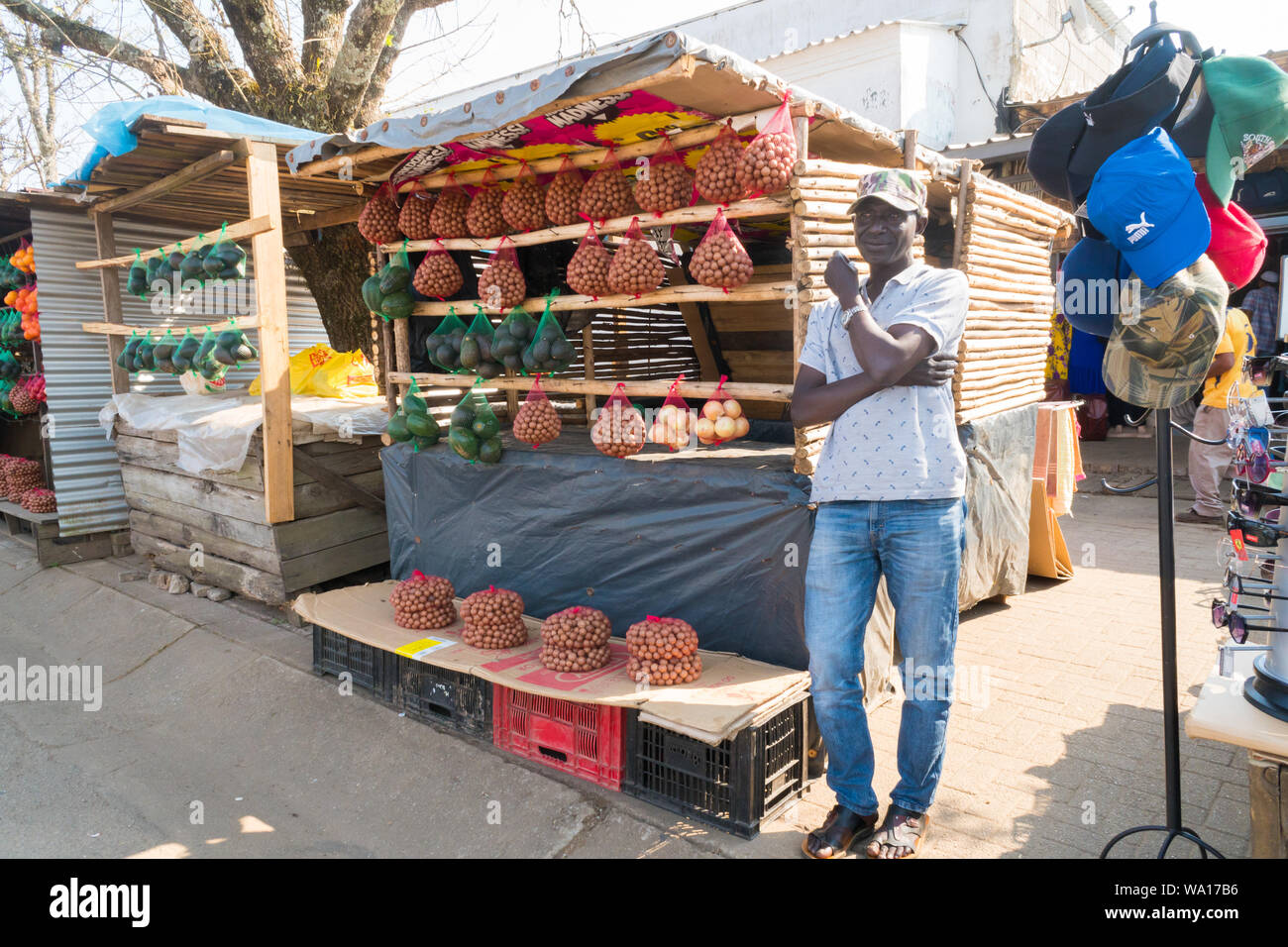 black African man street vendor stands at a fruit and vegetable stall which displays nuts, Avocado pears, onions in Graskop, Mpumalanga, South Africa Stock Photo