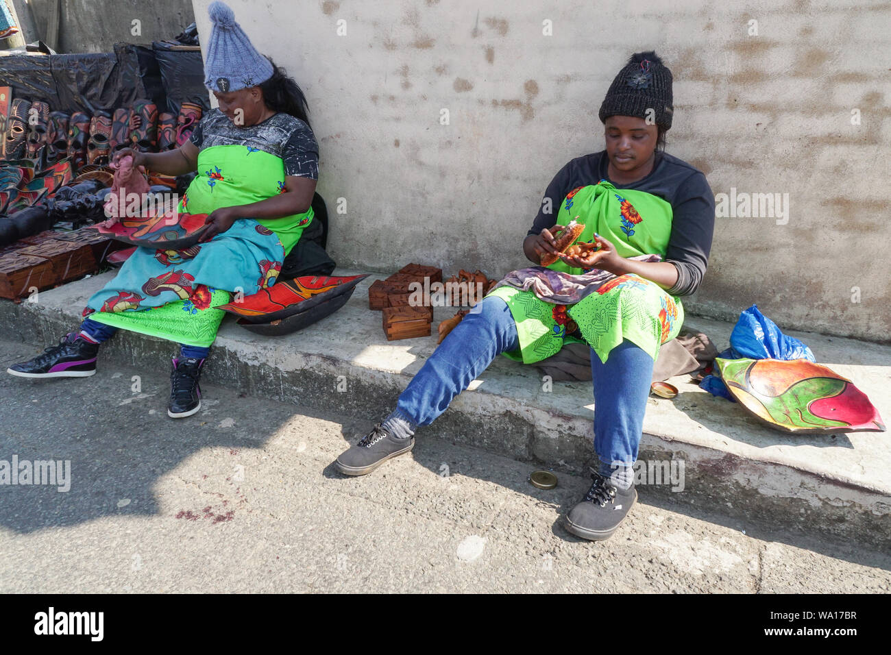two black African ladies or women street vendors sitting working on goods or wooden items outside their stalls in Gods Window,Mpumalanga, South Africa Stock Photo