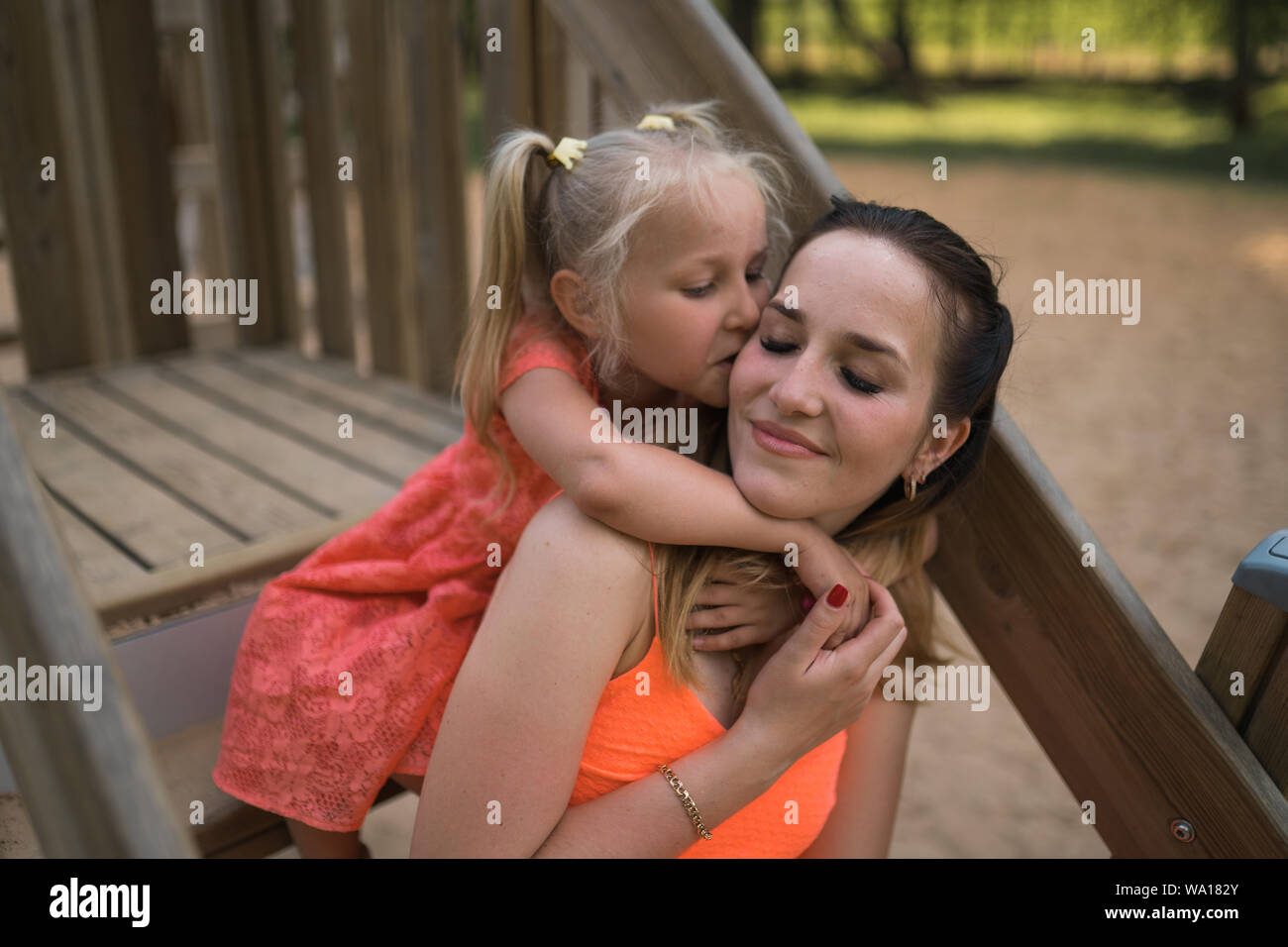Happy mother playing with her little baby girl daughter and having fun - Young caucasian white mom wearing summer bright vivid color dress - Stock Photo