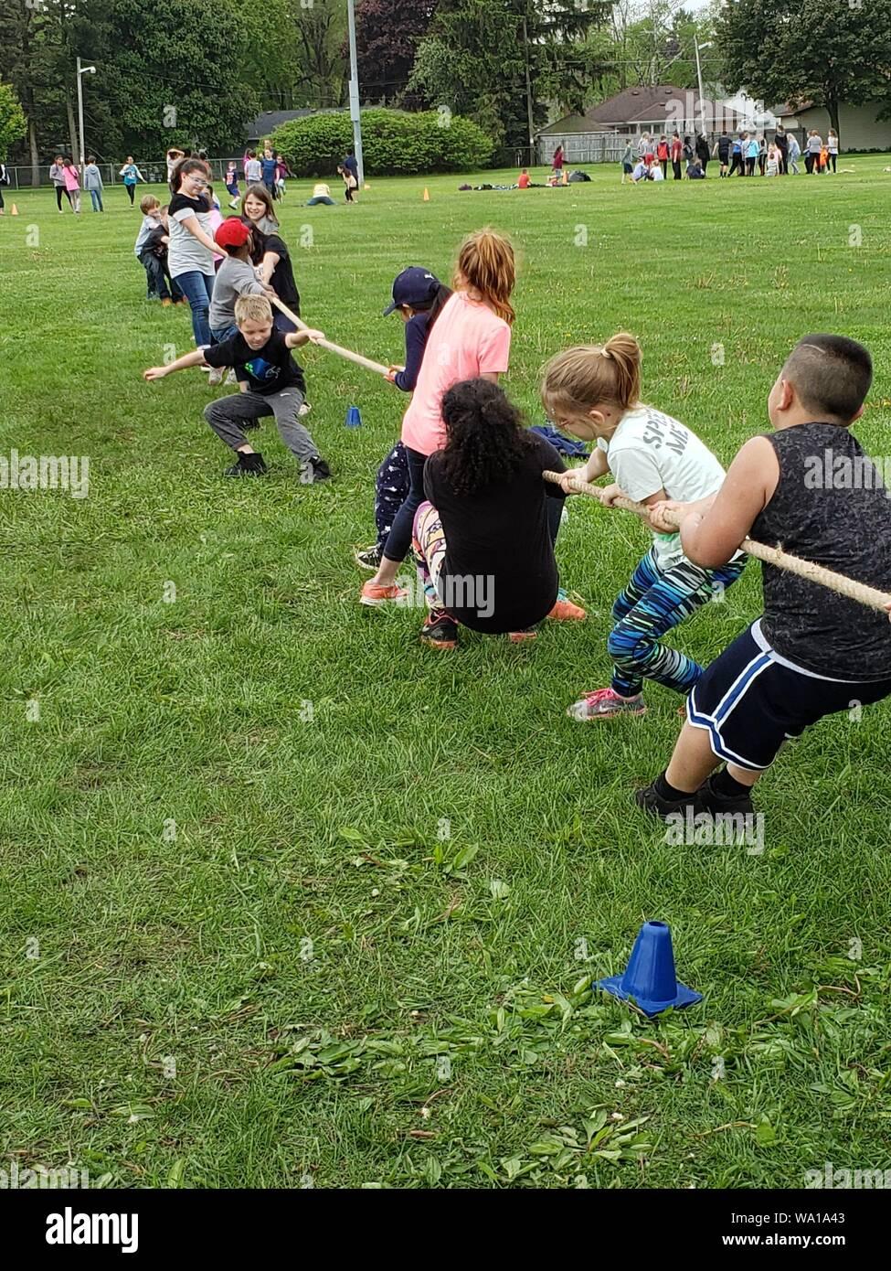 3rd grade students enjoying a fun game of tug-of-war. Stock Photo