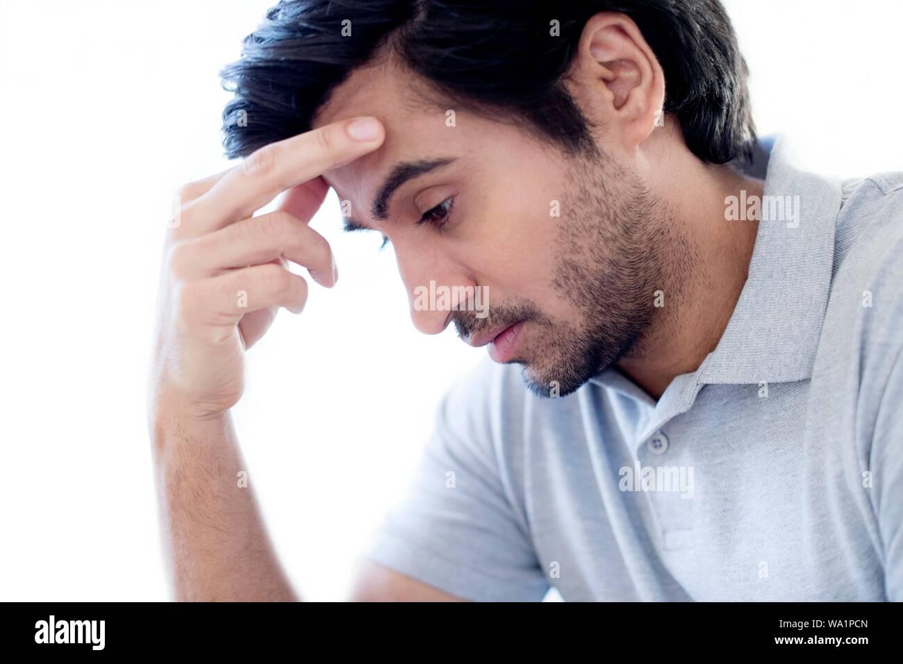 Man touching his forehead. Stock Photo
