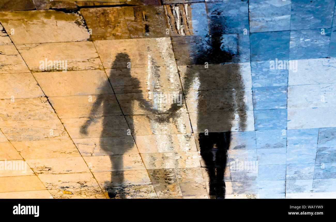 Blurry reflection shadow silhouettes of  a young couple walking on a wet street  on a sunny summer day in old town stone pavement Stock Photo