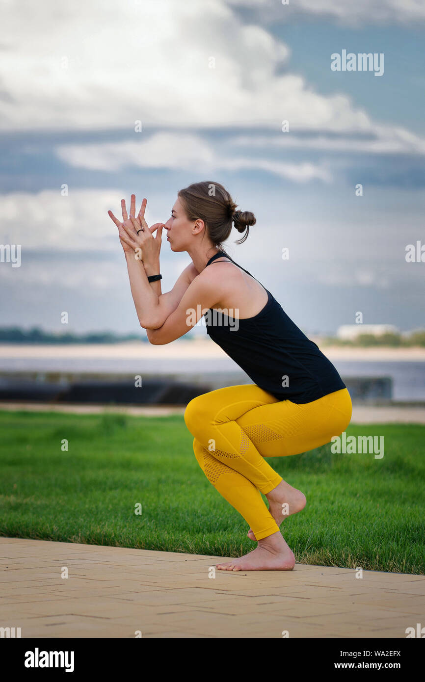 Young beautiful woman practicing yoga with cloudy sky in the background. Wellness concept. Calmness and relax, woman happiness. Yoga is the best holis Stock Photo