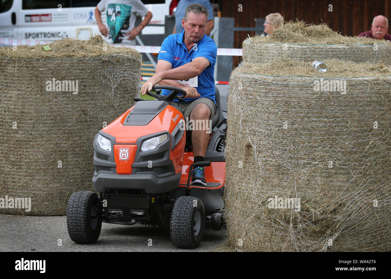 17 August 2019, Bavaria, Rückholz: A participant of the 1st Bavarian Championship in the riding mower obstacle race drives a course through hay bales during the race. In the Allgäu the 1st Bavarian Championship in the ride-on lawn mower obstacle course has begun. On Saturday (17.08.2019) more than 70 participants started in good weather until the afternoon. Photo: Karl-Josef Hildenbrand/dpa Stock Photo