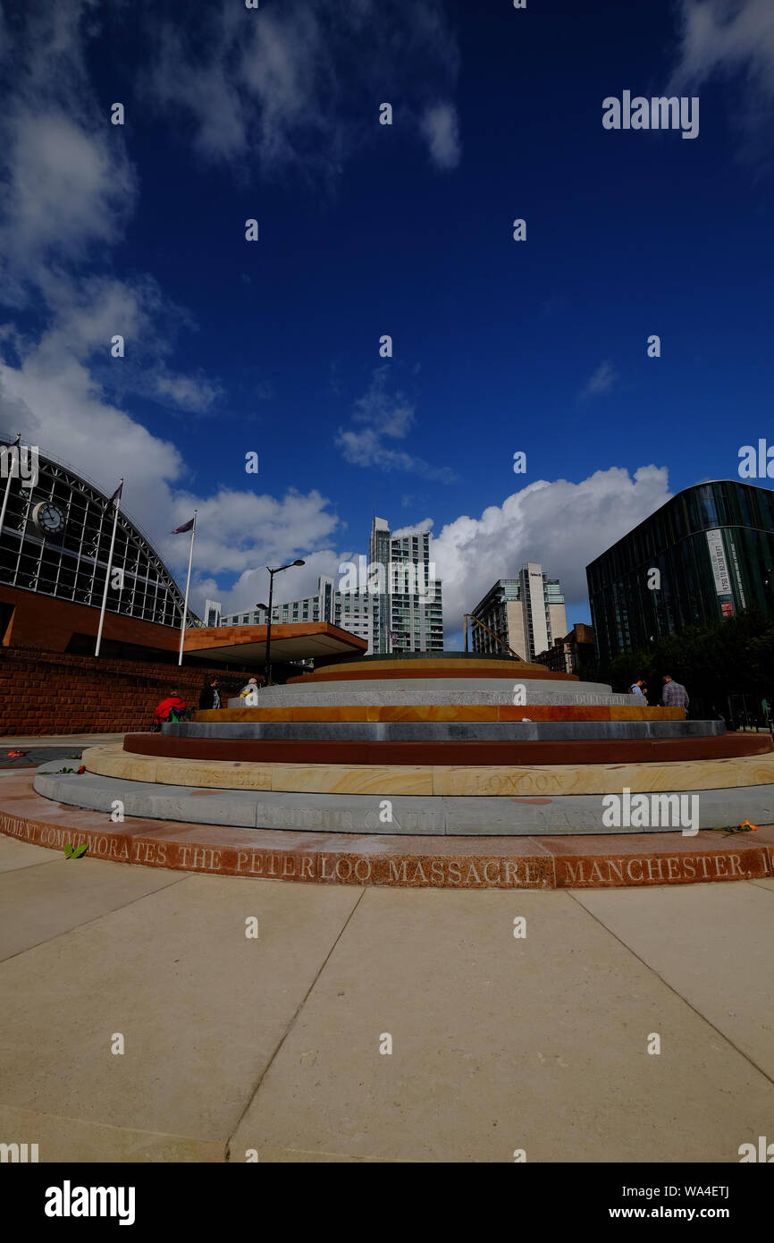 Portrait view of Peterloo Memorial Manchester in blue skies and sunshine with Manchester Central in background and people interacting. Stock Photo