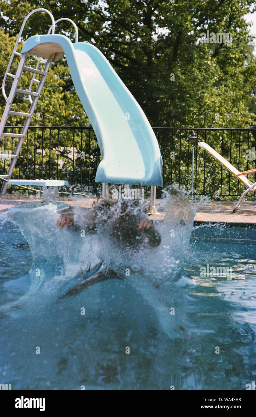 1977 - Young teen uses a pool slide in a residential ...