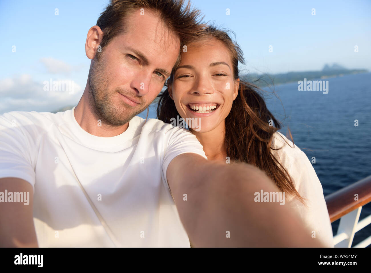 Selfie couple taking holiday self-portrait picture of themselves. Happy multiracial friends having fun together on cruise vacation in Caribbean destination taking smartphone photos as summer memories. Stock Photo