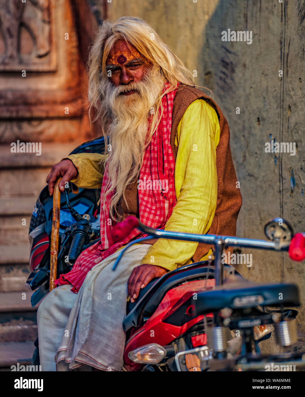 Vrindavan, India - February 22, 2018 - Old man sits on a motorcycle while holding a wooden cane Stock Photo