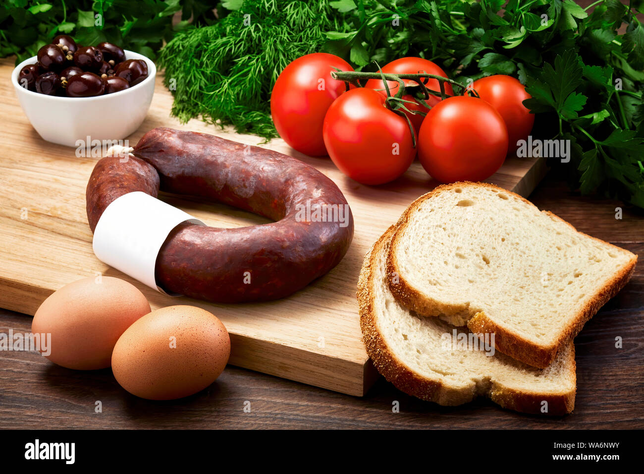 Turkish fermented sausage on wooden table with wooden cutting board with eggs, olive, parsley and tomatoes. Turkish breakfast. Stock Photo