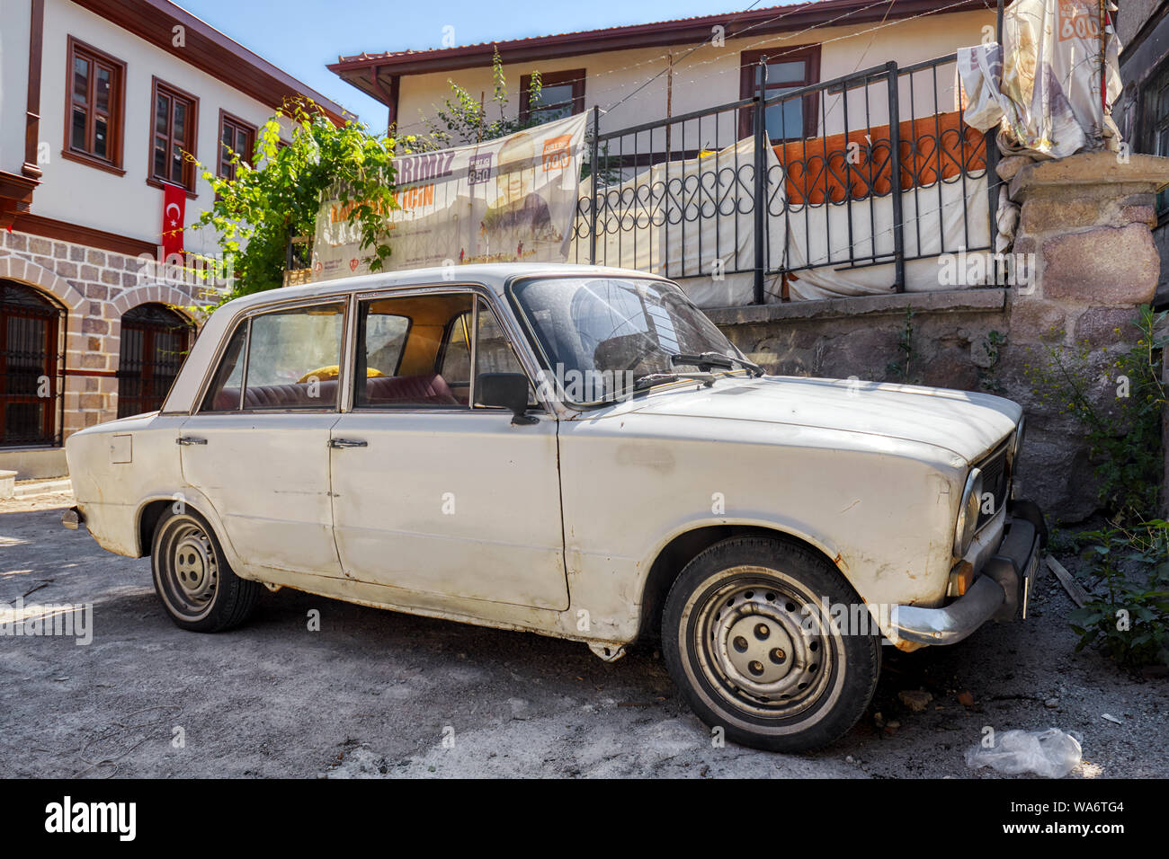 Vintage scrap Fiat 124 car parked in front of a shanty house in the ghetto of Hamamonu district, Ankara, Turkey. Stock Photo