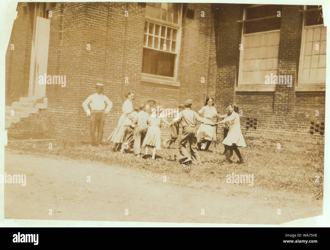 Ring around the rosy. Supt. and overseers with the Relief Crowd, in Yazoo City (Miss.) Yarn Mills. The Supt. said, We relieve all children under sixteen for two hours a day except the doffers. They go out and play. Then turning to the children he said, Now play. They eyed him blankly, Play wot Oh, play anything. Before they could do it, however, he had to pose them himself (see photo 2106) which was especially posed for the occasion. In this photo, note the disparity between the (alleged) ages of the younger ones who said that they were 12 and thirteen, and the older ones, who said fifteen yea Stock Photo
