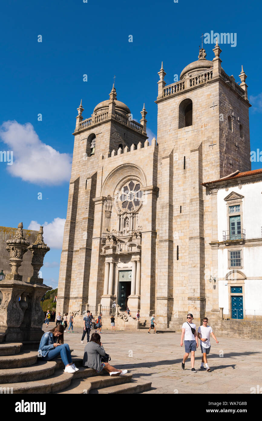 Portugal Oporto Porto Sé do Porto Sé Cathedral clock square tower facade clouds entrance door steps stairs cupola museum tourists trees Stock Photo