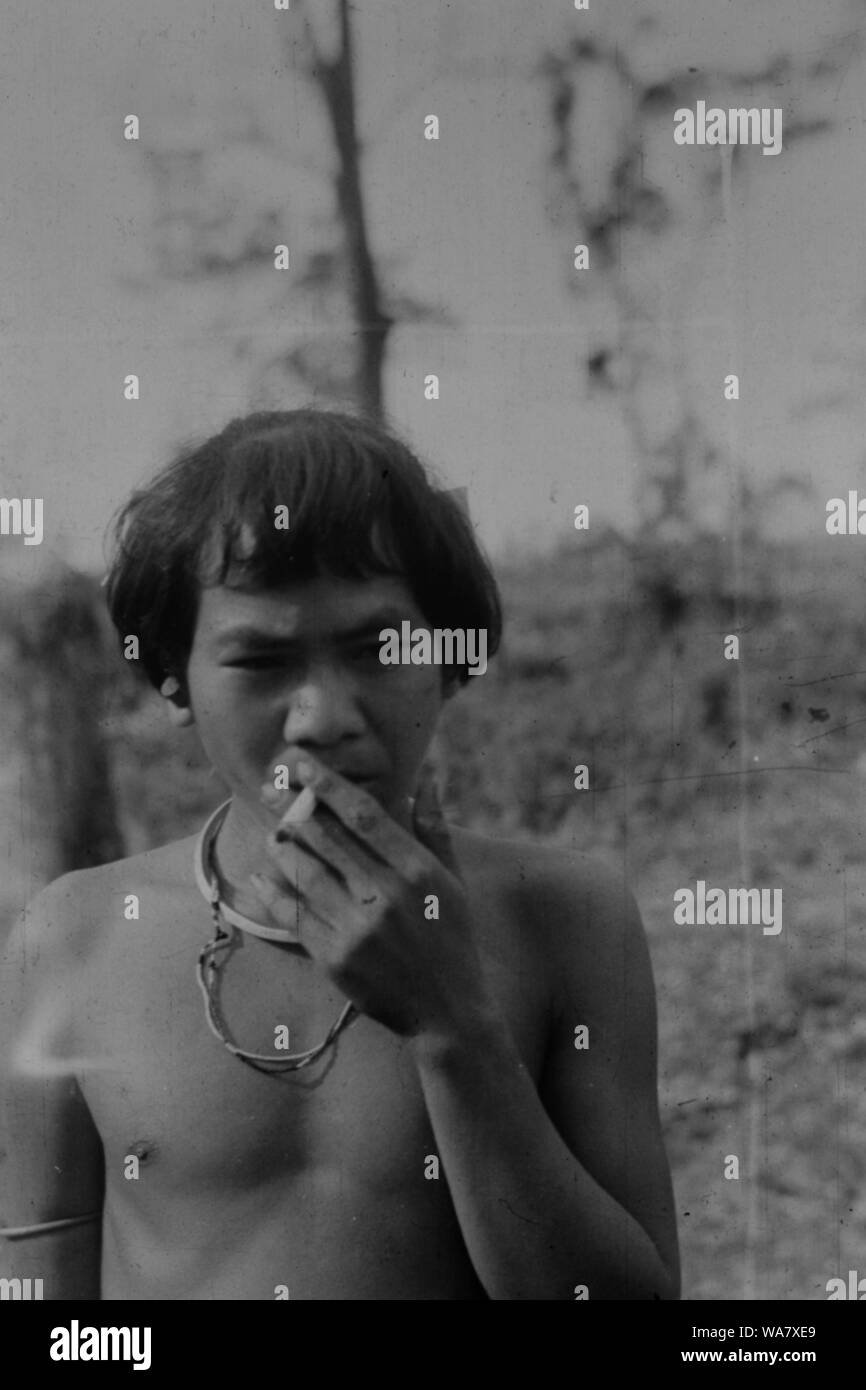 AJAXNETPHOTO. 1953-1957 (APPROX). INDO CHINA. VIETNAM. (IN-COUNTRY LOCATION UNKNOWN.) - A TRIBESMAN, POSSIBLY MONTAGNARD, SMOKING A CIGARETTE. PHOTO:JEAN CORRE/AJAXREF:RX7 191508 256 Stock Photo