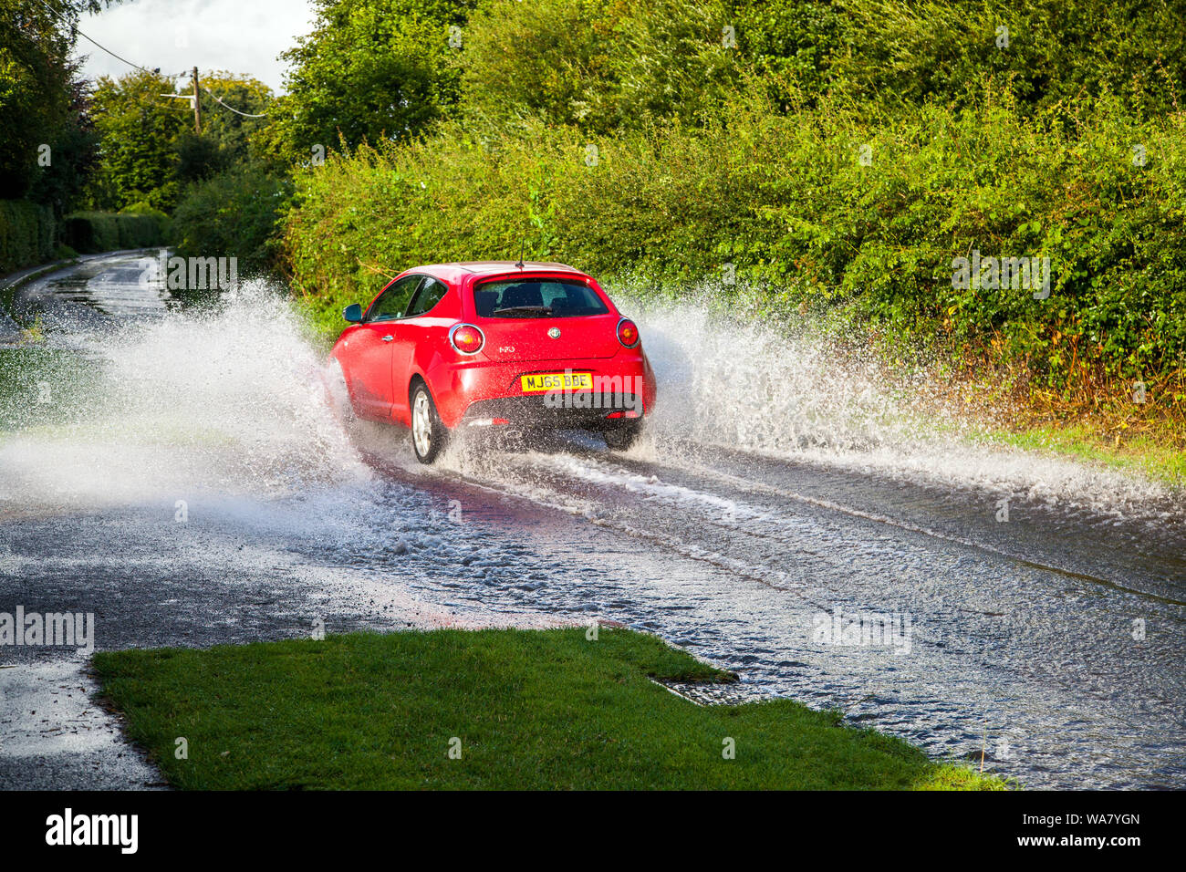 Car driving through water along a flooded country road / lane during wet weather after a heavy rain storm Stock Photo
