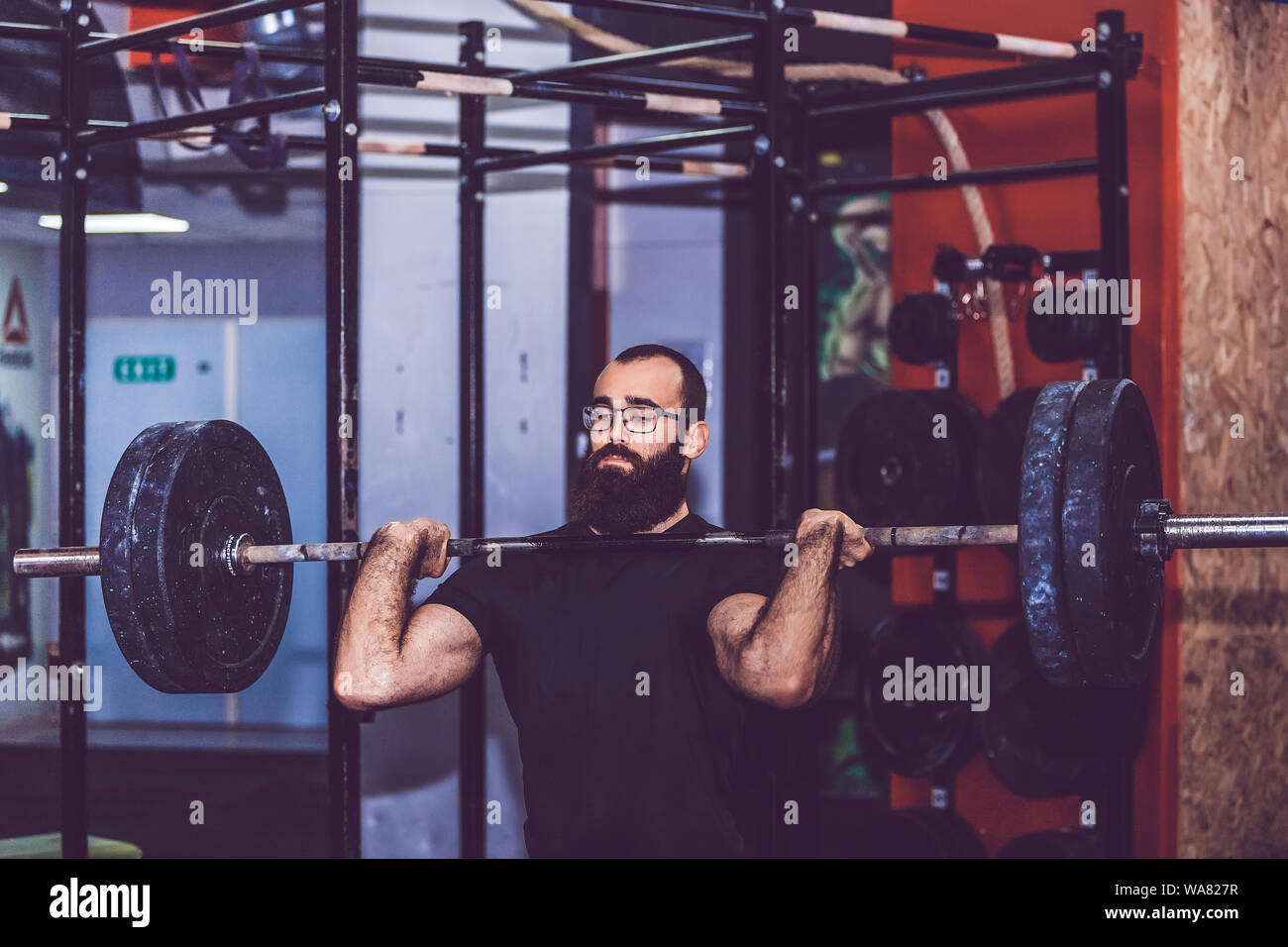 Young bearded man straining to lift heavy weights during a workout session in a gym Stock Photo