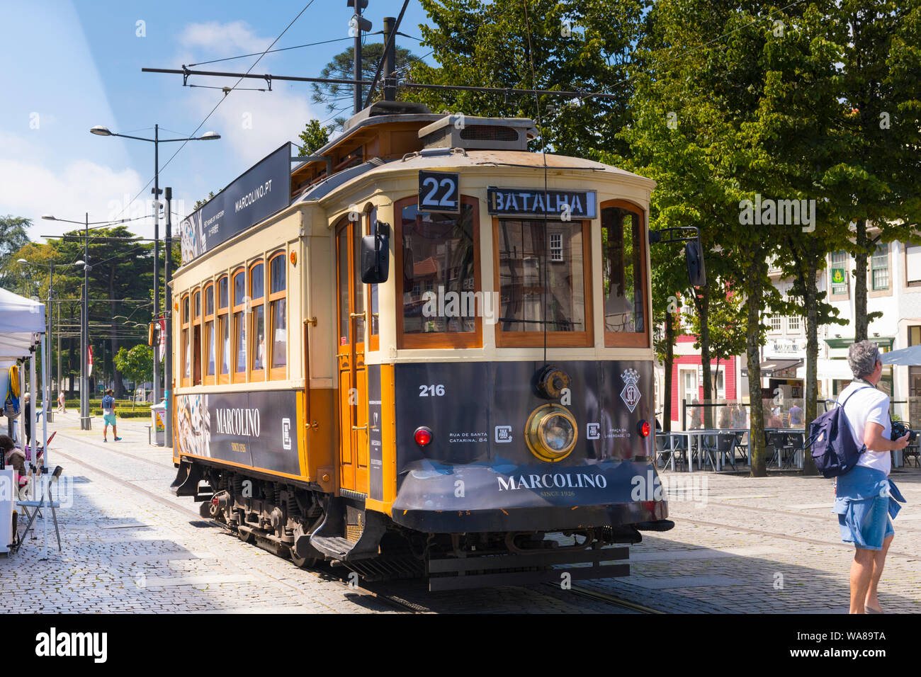 Portugal Oporto Porto old No 22 tram streetcar to Batalha tramlines rails street scene wooden doors window frames trees cafe Stock Photo
