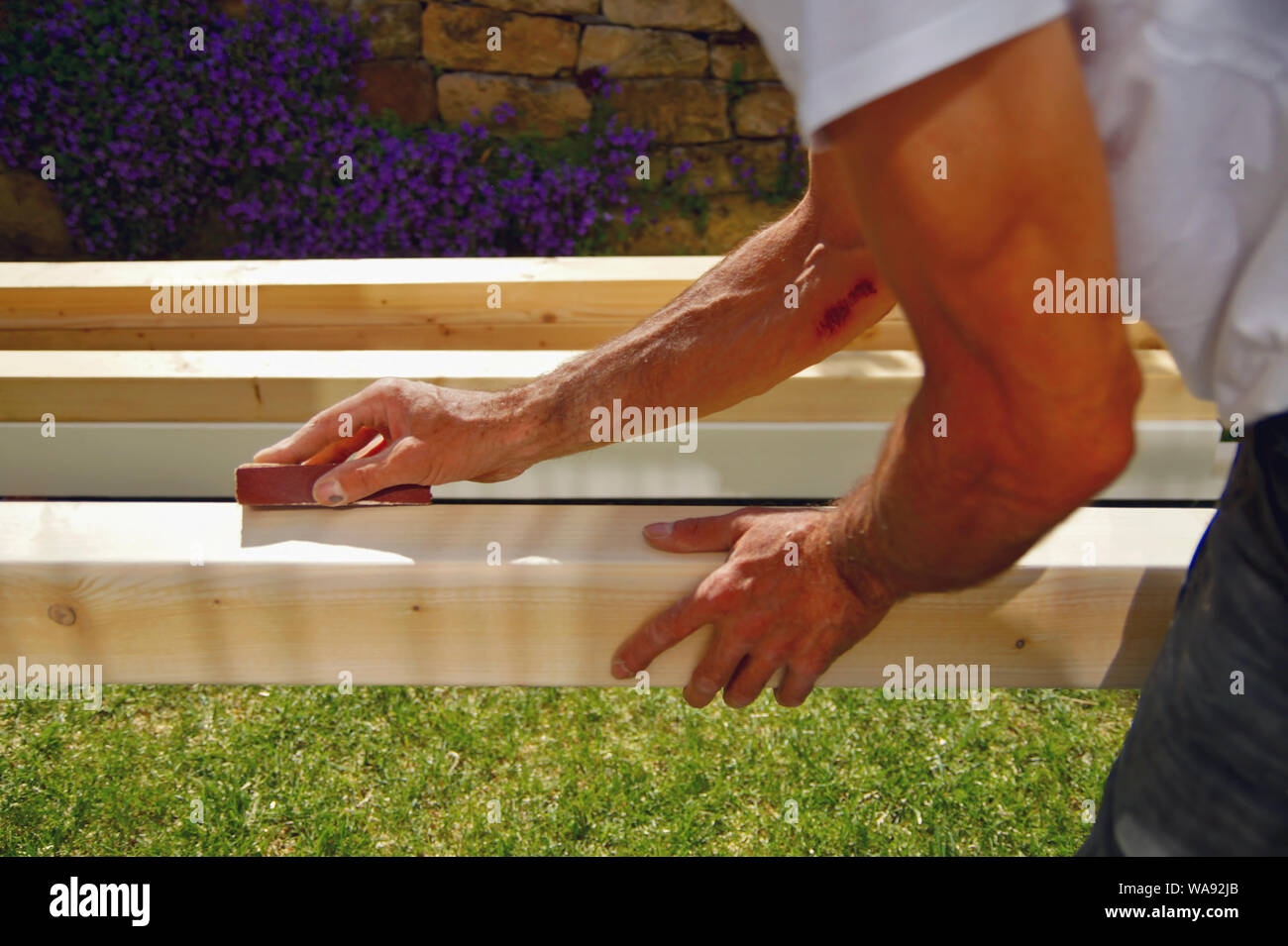 man's hand smoothing natural wooden beam using sandpaper while he is  working outside. Sanding of wood beams spruce for carport. Stock Photo