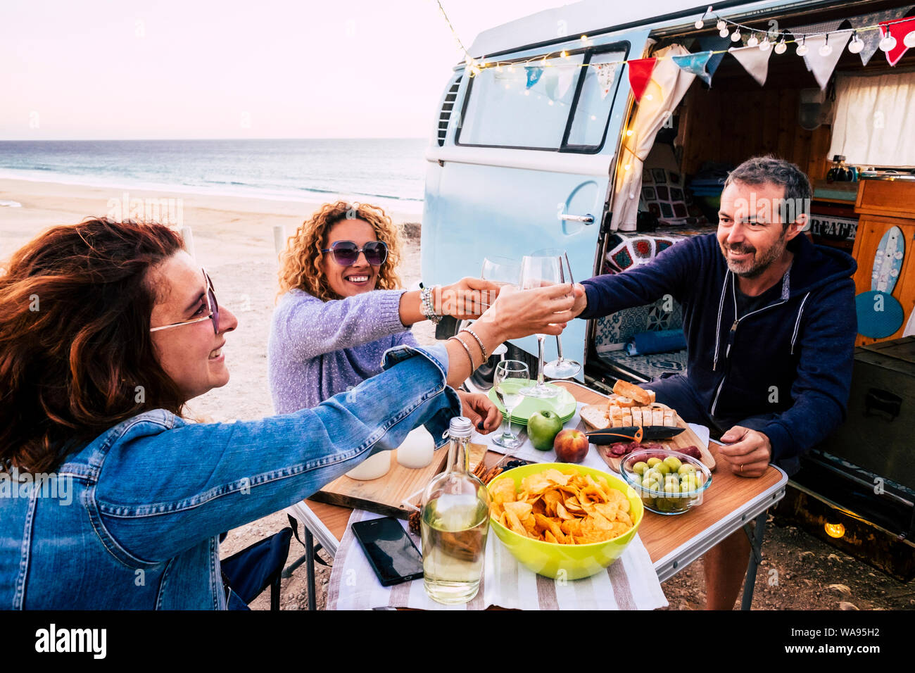 Happy people group of friends toasting and enjoying the travel vacation together - cheerful. womanandman with food in outdoor leisure activity - old v Stock Photo
