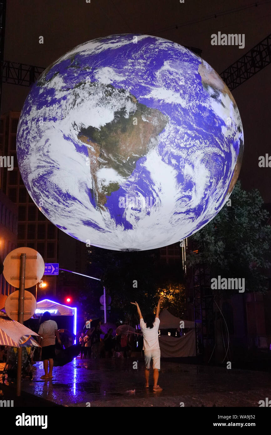 Visitors Interact With Gaia An Artistic Installation Of Glowing Earth By Uk Artist Luke Jerram Erected At The Bund In Memory Of 50th Anniversary Of Stock Photo Alamy