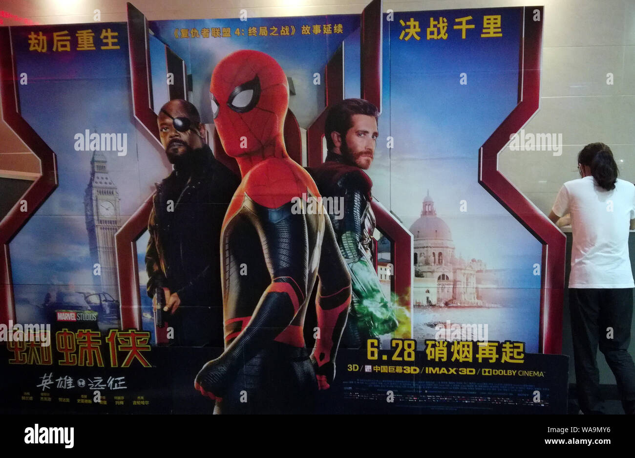 """A filmgoer waits in front of a poster of American superhero film """"Spider-Man: Far from Home"""" at a cinema in Yichang city, central China's Hubei provin Stock Photo"""
