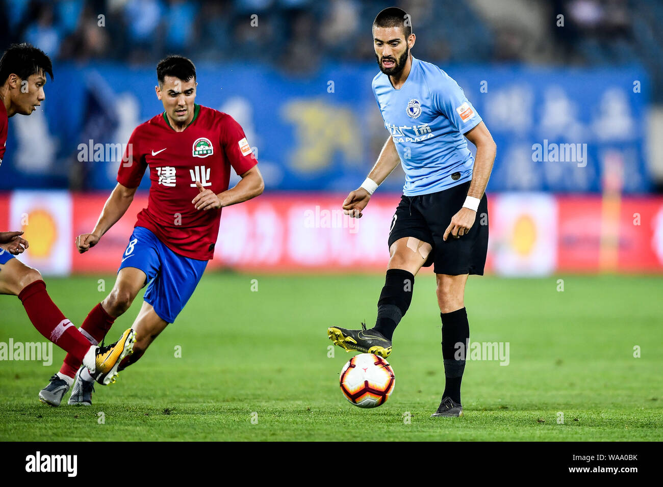 Belgian football player Yannick Ferreira Carrasco, right, of Dalian Yifang passes the ball against English-born Taiwanese football player Tim Chow of Stock Photo