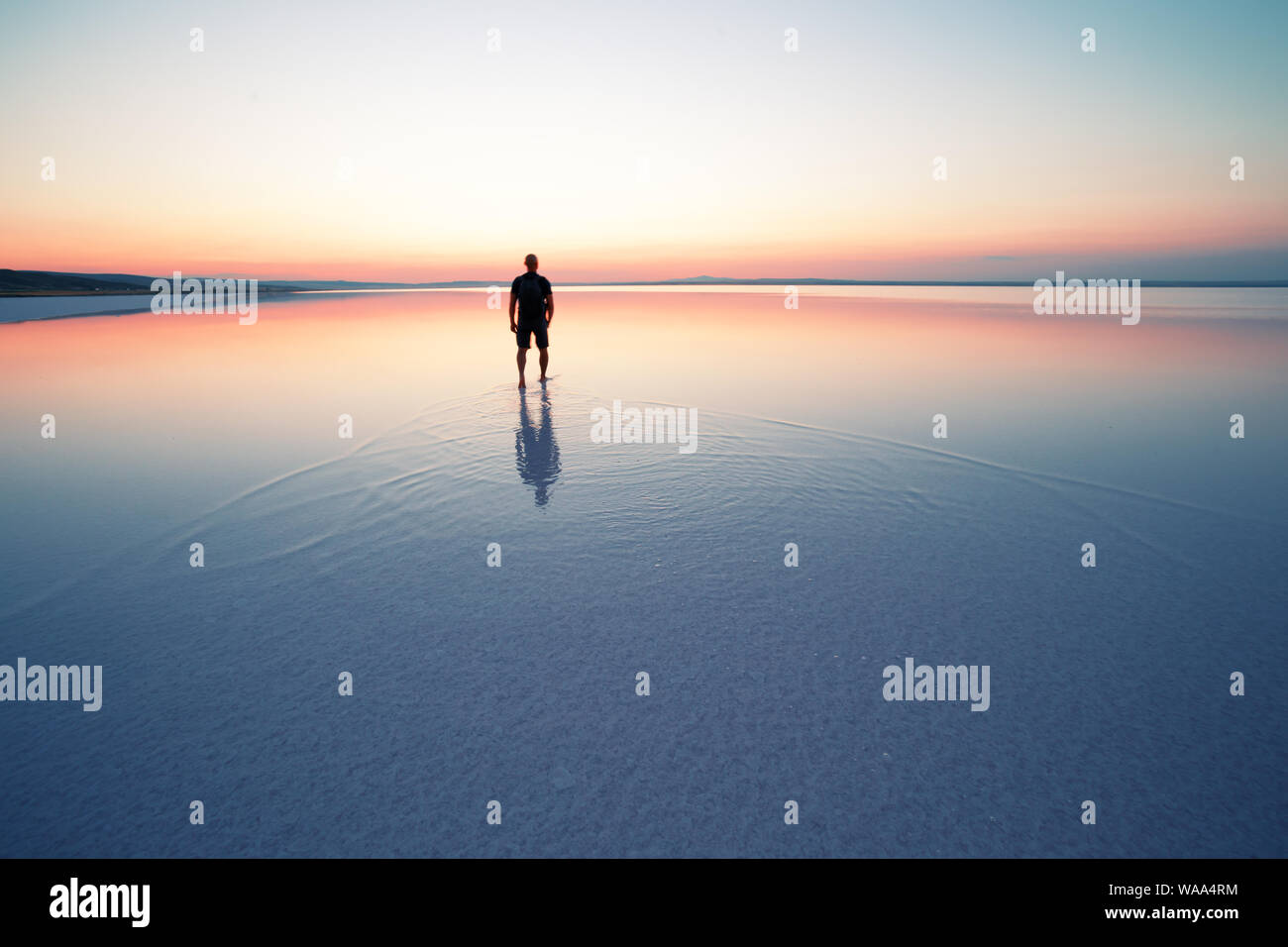 Silhouette of man departing into sunset on smooth water of lake Stock Photo