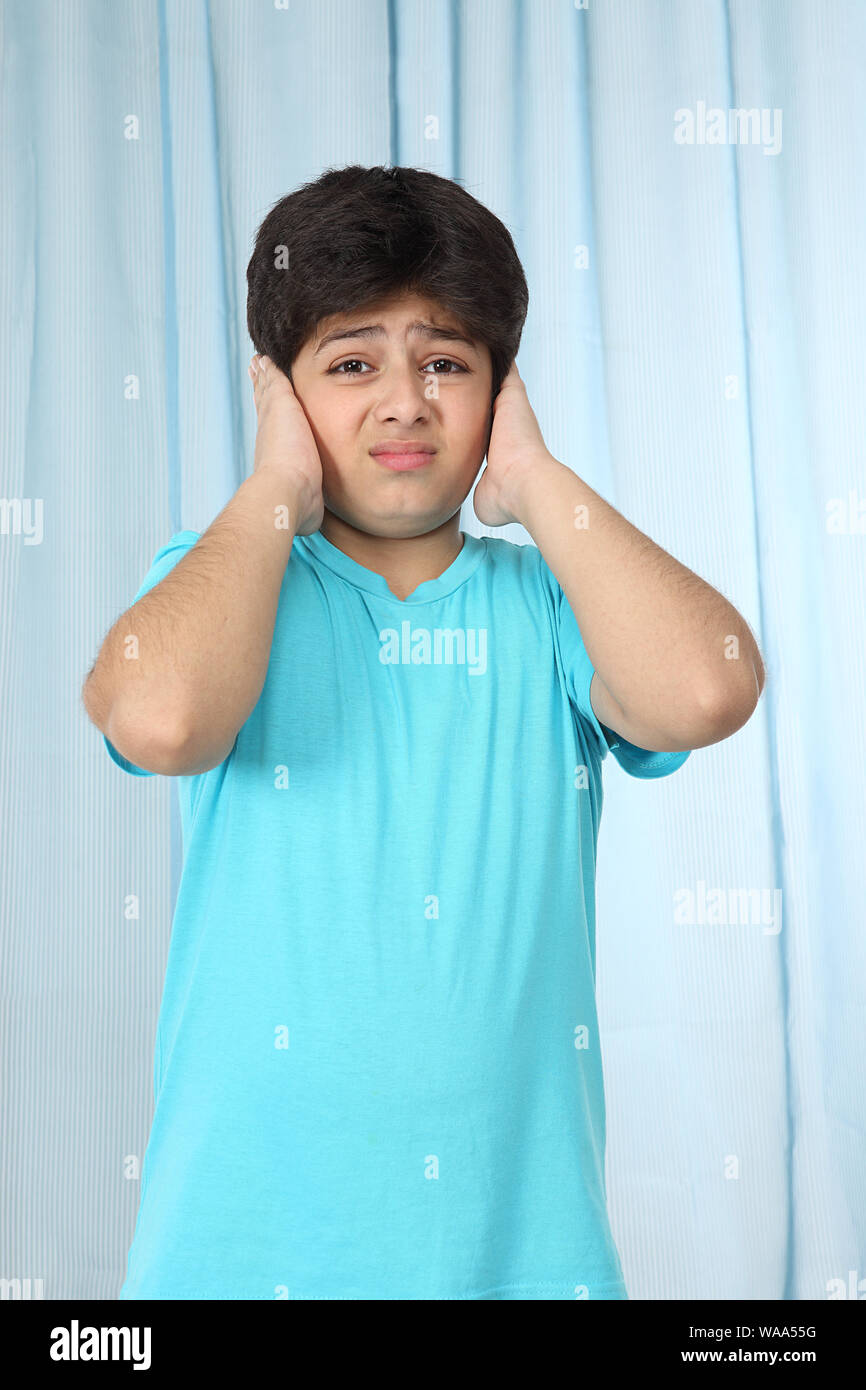 Boy covering ears with hands Stock Photo