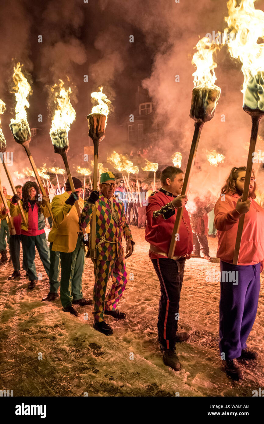 Men in colourful fancy dress costumes parade through the snowy streets of Lerwick carrying fire torches at the 2019 Up Helly Aa festival in Shetland Stock Photo