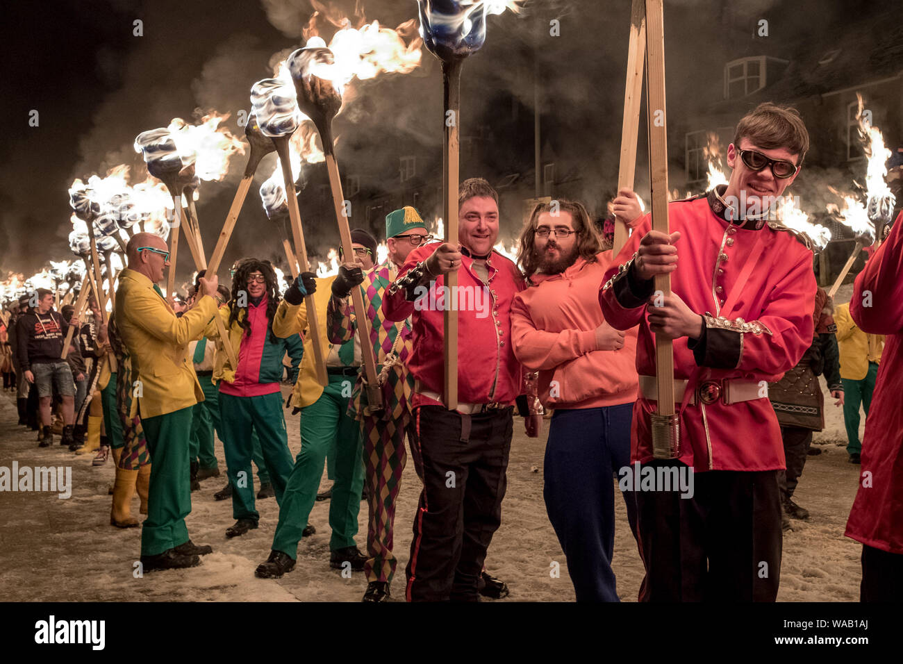 Men in various fancy dress costumes holding fire torches pose for the camera at the 2019 Up Helly Aa festival in Lerwick, Shetland Stock Photo