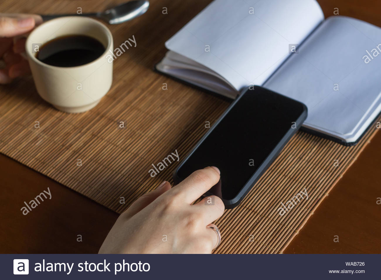 A woman with her smart phone having a cup of coffee and planning business with a notebook Stock Photo