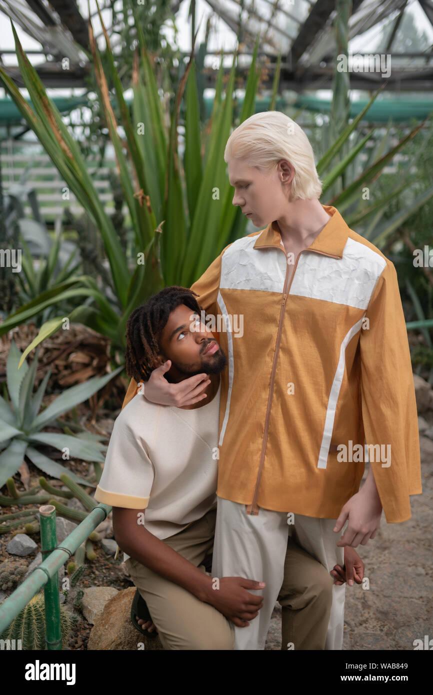 Blonde Male Model Looking At Dark Skinned Man Stock Photo Alamy