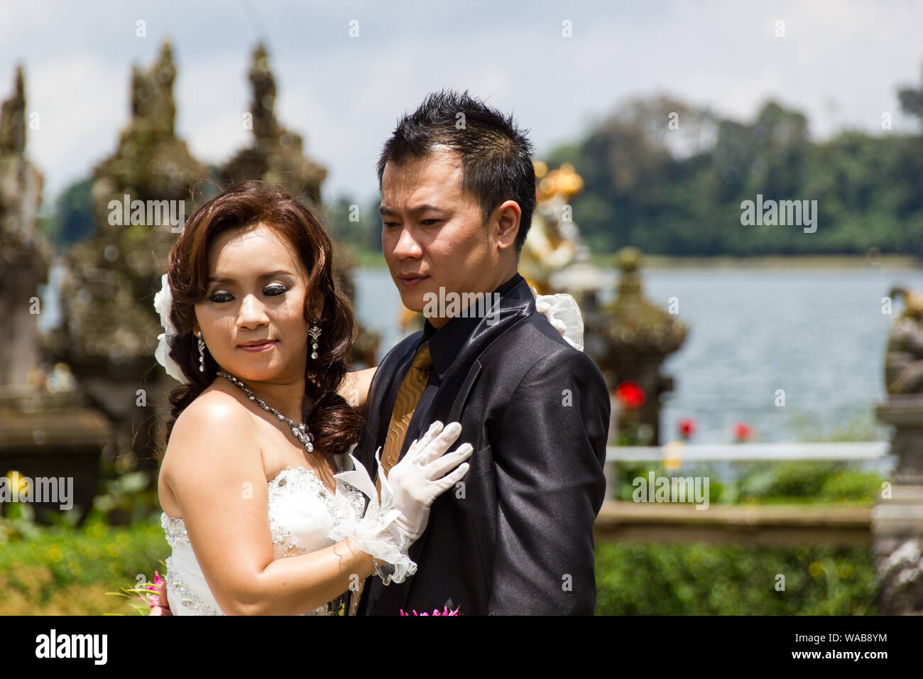 Bali, Indonesia - Mar 25th, 2014  - Newlywed Chinese couple  posing for photos at  Pura Ulun Danu Bratan, Bali. Hindu temple surrounded by flowers on Stock Photo