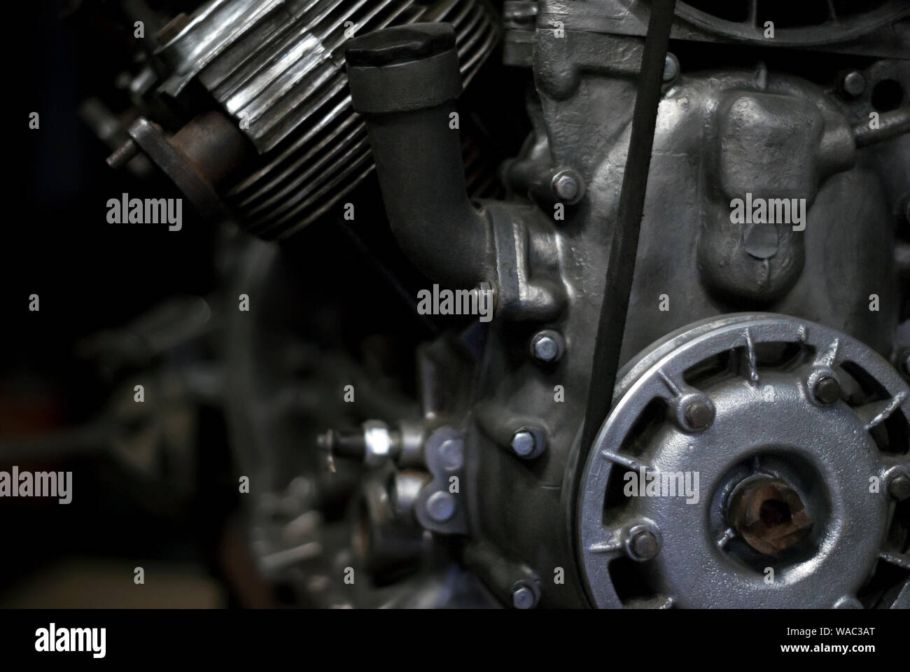 fragment of a semi-assembled internal combustion engine on a dark background Stock Photo