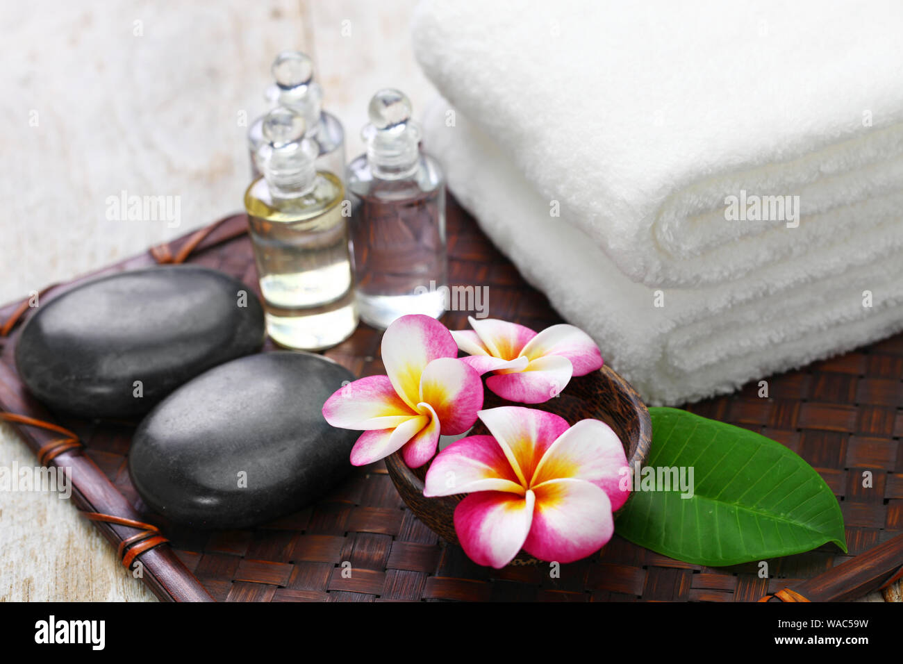 tropical spa resort concept; plumeria, hot stones, towels, and massage oils Stock Photo