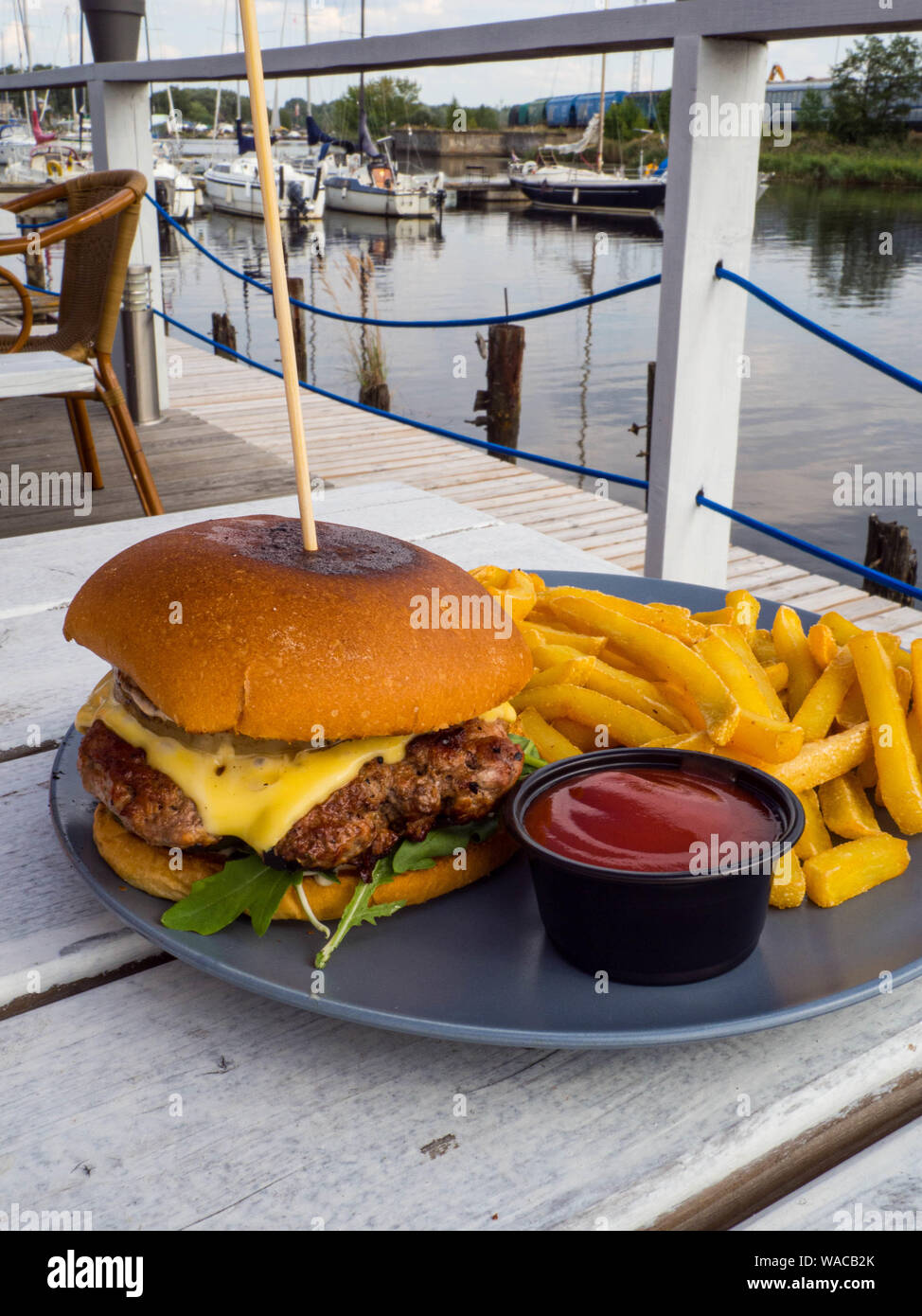 tasty burger with french fries and ketchup outdoor in wooden