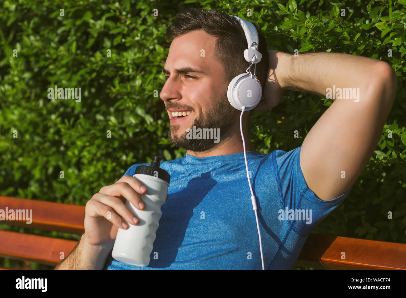 Handsome man with headphones  drinking water and resting after exercise in the park. Stock Photo