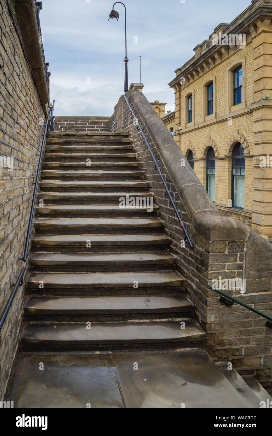 Millworkers steps outside Salts Mill in Saltaire, Yorkshire.The steps lead from the outside of the mill up to the pavement. Stock Photo