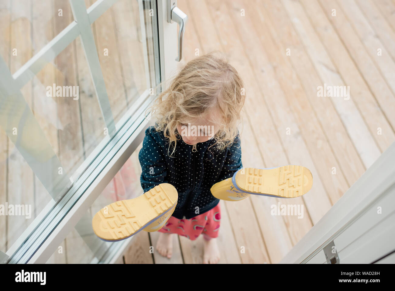 girl standing in the doorway looking at the rain boots on her  hands Stock Photo