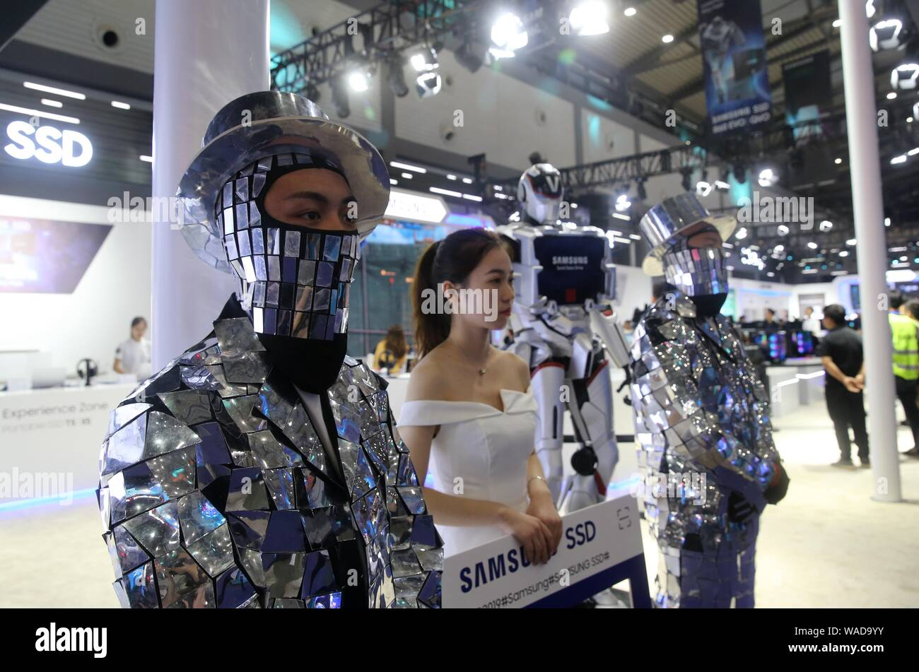 Employees pose at the stand of Samsung during the WCG 2019