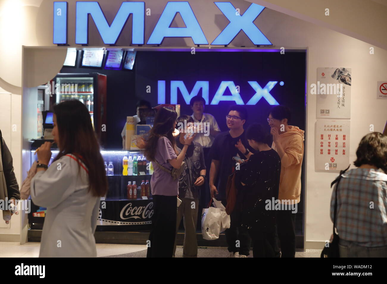 """--FILE--Chinese filmgoers wait inside a cinema featuring IMAX before the midnight premiere of Disney and Marvel's """"Avengers: Endgame"""" in Shanghai, Chi Stock Photo"""