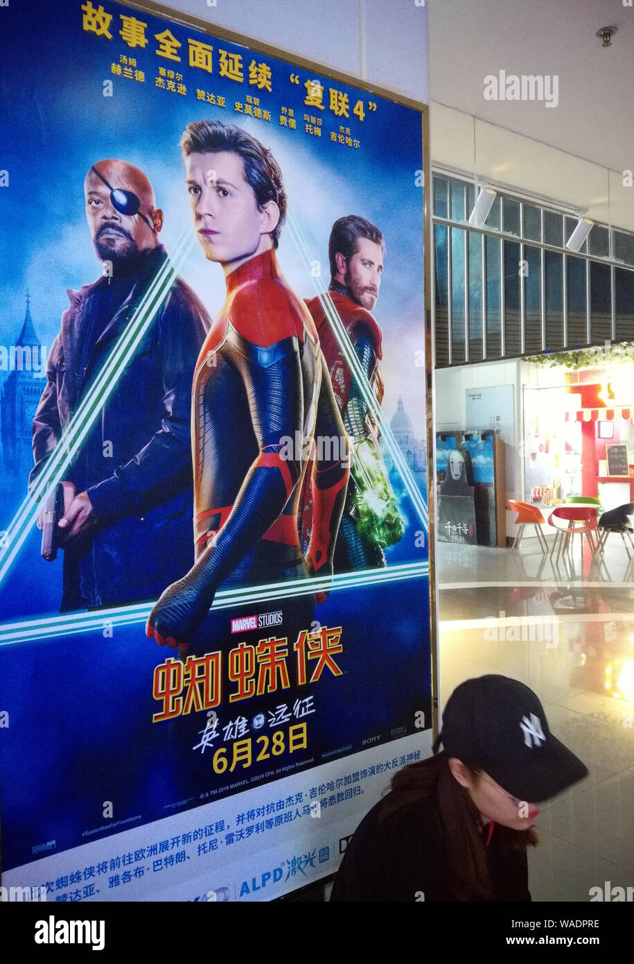 "--FILE--A filmgoer waits in front of a poster of American superhero film ""Spider-Man: Far from Home"" at a cinema in Yichang city, central China's Hube Stock Photo"